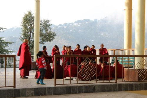 A Tibetan girl watches boys learning dialectics at the Tsuglag Khang temple in Dharamsala